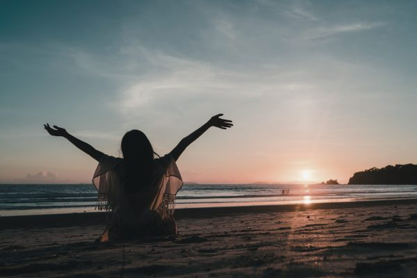 Young Asian woman watching sunset near beach, beautiful female happy relax enjoy moment when sunset in evening. Lifestyle woman travel on beach concept.